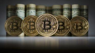 bitcoin in front of dollar bills