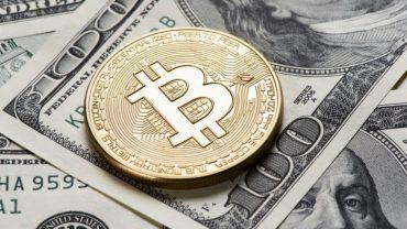 bitcoin phisycal coin above a dollar 100 bill