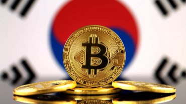 phisycal bitcoin in front of south korea flag