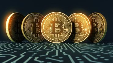 phisycal bitcoins above electrical circuit
