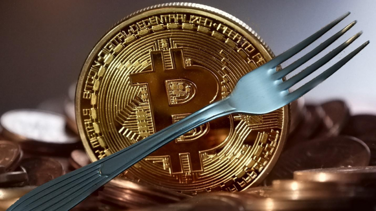 phisycal bitcoin with a fork in front of it, illustration a hard fork of bitcoin