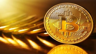 golden bitcoin with staked bitcoin in the back