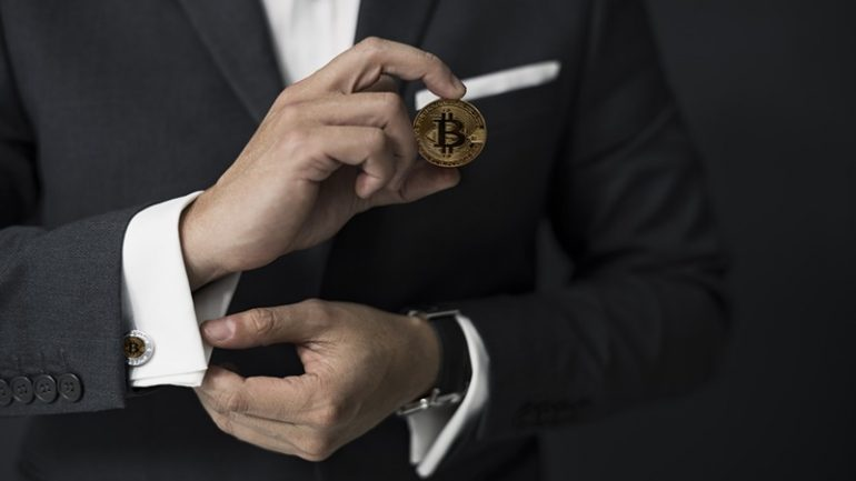 man holding a bitcoin in hand