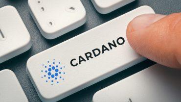 finger pressing computer key with cardano coin logo.