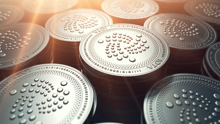 IOTA coins in blurry closeup with sunburst from above