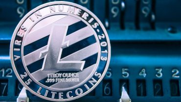 Coin of litecoin on the background of numbers adding machine