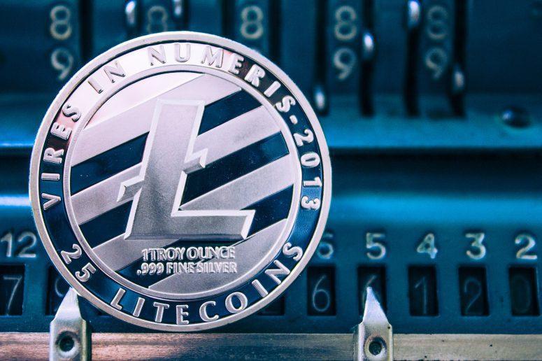 Mynt av litecoin på bakgrunden av nummer som adderar maskinen