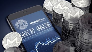 Smartphone with Monero trading chart on-screen among piles of silver Monero coin