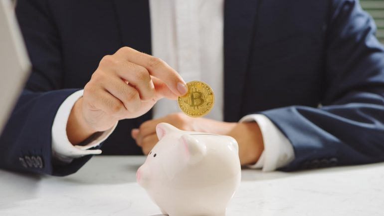 Investor holding Bitcoin above a piggy bank