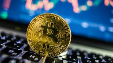 phisycal bitcoin on computer keyboard