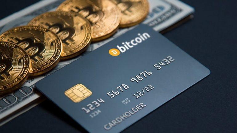 phisical bitcoin on 100 dollar bills near a bitcoin credit card