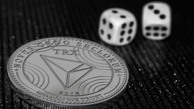 Tron phisycal coin and two dice near it