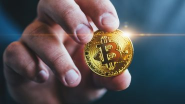 Cryptocurrency golden bitcoin coin in man hand