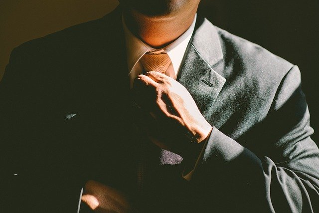 man placing his tie