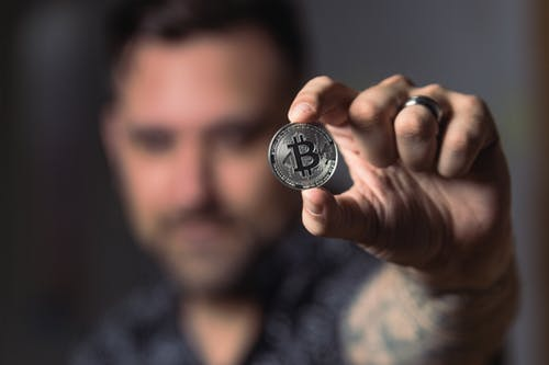 Man showing a phisycal bitcoin