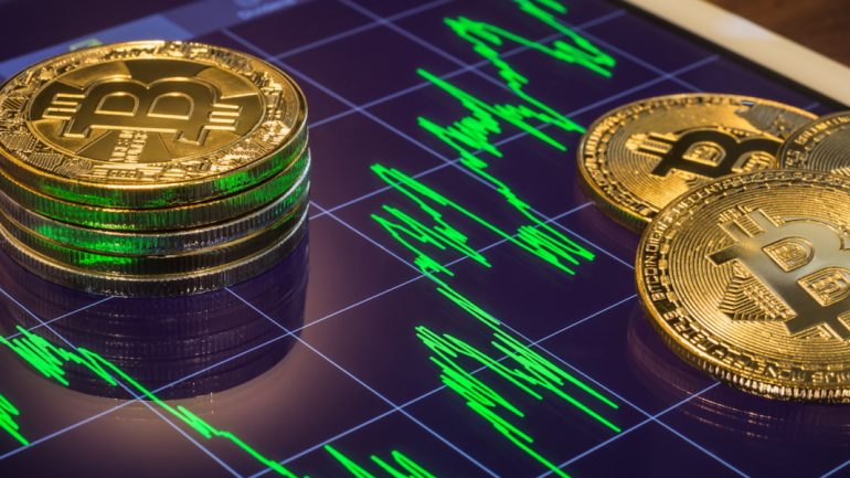 phisycal bitcoins placed above a trading graph