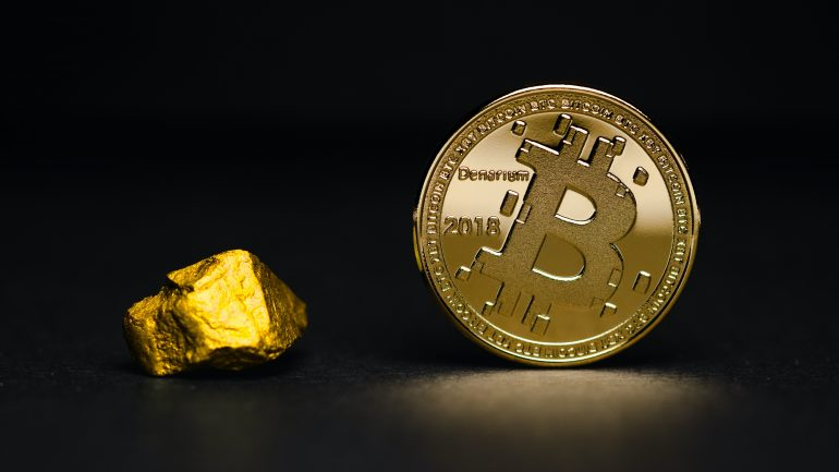 Bitcoin next to piece of gold