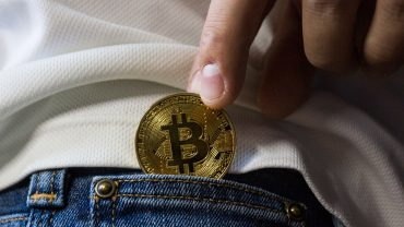 hand puts bitcoin in back pocket