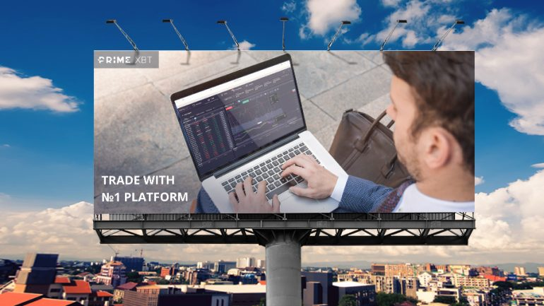 billboard showing guy sitting on the pavement and trading on a laptop