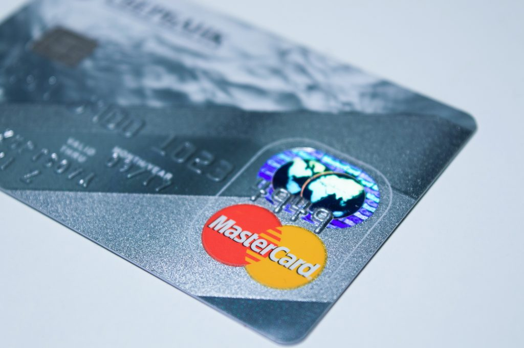 A MasterCard card stands in a grey background