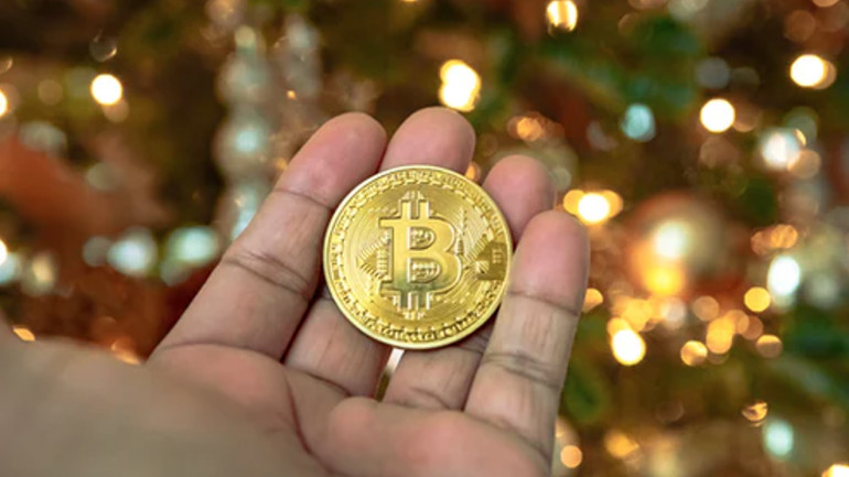 Hand holding a Bitcoin coin that allows users to know what is a satoshi (each BTC is worth 100 million satoshis)