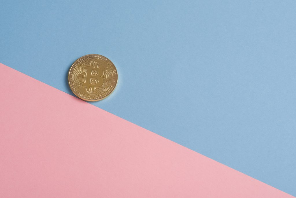 bitcoin coin with a baby blue and pinky background that helps users understand what is a satoshi