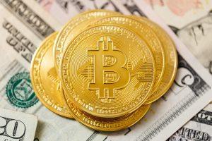Bitcoin with dollar banknotes behind