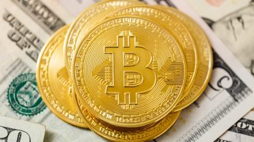 Bitcoin with dollar banknotes behind - free bitcoin sites